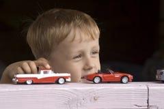 Weinig jongen speelt een stuk speelgoed auto Stock Foto's