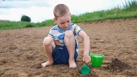 Weinig jongen speelt het graven van een kuil met een schop Het spelen van het jonge geitje op het strand stock videobeelden