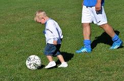 Weinig jongen speelt met een voetbalbal stock fotografie