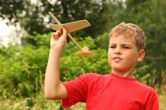Weinig jongen speelt met houten vliegtuig op aard stock foto