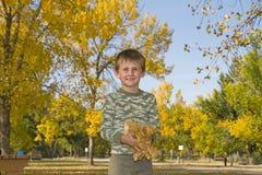 Weinig jongen speelt met kleurrijke bladeren in lucht Stock Foto's