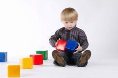 Weinig jongen speelt met kleurrijke kubussen royalty-vrije stock foto