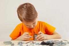 Weinig jongen speelt met metaalaannemer bij lijst Stock Foto's