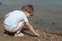 Weinig jongen speelt met stenen Stock Fotografie