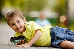 Weinig jongen speelt met stuk speelgoed auto Royalty-vrije Stock Afbeeldingen