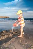 Weinig jongen speelt met water op een strand Royalty-vrije Stock Afbeeldingen