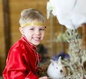 Weinig jongen speelt met witte Paashaas op de groene gras en babykonijntjes, de Lentefestival en geboorte royalty-vrije stock fotografie