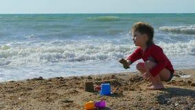 Weinig jongen speelt op het strand in het zand en het opscheppen stock video