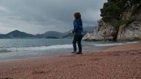 Weinig jongen speelt in openlucht met golven op kust stock footage