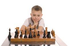 Weinig jongen speelt schaak Stock Foto's