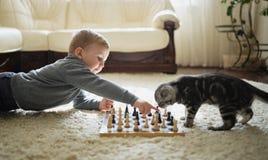 Weinig jongen speelt schaak liggend op vloer Stock Afbeelding
