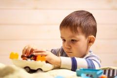 Weinig jongen speelt thuis met stuk speelgoed auto royalty-vrije stock afbeeldingen