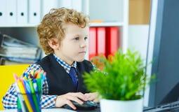 Weinig jongen speelt in werkgever, die bij computer werken stock afbeeldingen