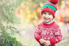 Weinig jongen in sweater en hoed die op Kerstmis in het hout wachten Stock Foto
