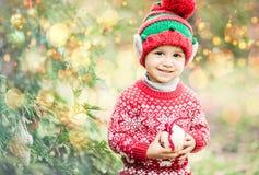 Weinig jongen in sweater en hoed die op Kerstmis in het hout wachten Royalty-vrije Stock Fotografie