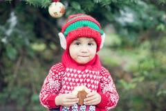 Weinig jongen in sweater en hoed die op Kerstmis in het hout wachten Royalty-vrije Stock Foto's