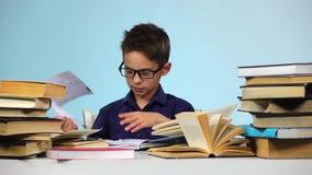 Weinig jongen trekt bladen van boeken terug Achtergrond voor een uitnodigingskaart of een gelukwens Langzame Motie stock videobeelden