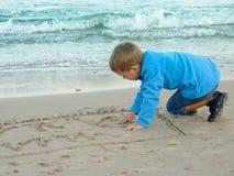 Weinig jongen trekt op zand stock foto's