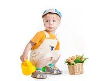 Weinig jongen in tuinman eenvormige zitting op witte achtergrond Stock Afbeeldingen