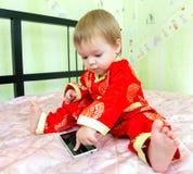 Weinig jongen in vakantiekostuum raakt het telefoonscherm Royalty-vrije Stock Afbeeldingen