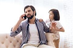 Weinig jongen vereist aandacht van bezige vader stock foto