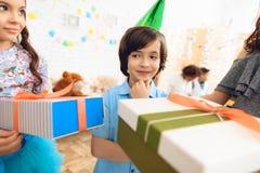 Weinig jongen verheugt zich op het ontdekken van giften die worden gegeven aan hem voor verjaardag stock foto's