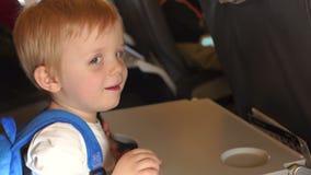Weinig jongen vermindert de lijst in het vliegtuig stock footage