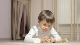 Weinig jongen verzamelt de ontwerper op de vloer stock video