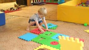 Weinig jongen verzamelt een groot raadsel op speelplaats stock video