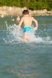 Weinig jongen in water Stock Foto's