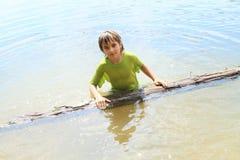 Weinig jongen in water met boomstam Stock Afbeeldingen