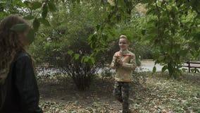 Weinig jongen werpt de herfstbladeren op het meisje in park stock videobeelden
