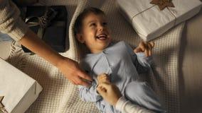Weinig jongen wordt gekieteld terwijl hij op de vloer onder de Kerstboom in langzame motie ligt stock footage