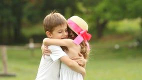 Weinig jongen zacht koestert het meisje, zijn zij gelukkig en onbezorgd Langzame Motie stock video