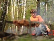 Weinig jongen zit dichtbij kampvuur Royalty-vrije Stock Foto's