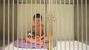 Weinig jongen zit in een kooi met een kat stock videobeelden