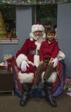 Weinig jongen zit op de overlapping van de Kerstman bij Kerstmisdiner voor de Militairen van de V.S. op Gewond Strijderscentrum,  stock afbeelding