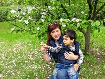 Weinig jongen zit op de overlapping van mamma in de tuin Royalty-vrije Stock Fotografie