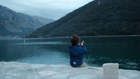 Weinig jongen zit op kust en werpt stenen in openlucht in water stock videobeelden