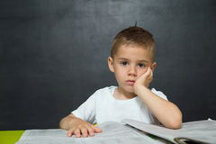 Weinig jongen zoals zakenman in bureau met krant Royalty-vrije Stock Fotografie