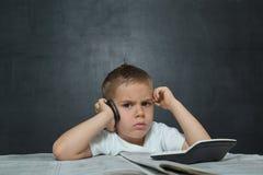Weinig jongen zoals zakenman in bureau met krant Royalty-vrije Stock Foto