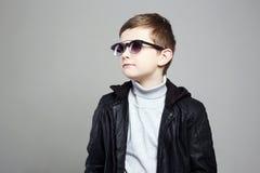 Weinig jongen in zonnebril modieus jong geitje in leer stock afbeeldingen