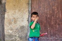 Weinig jongen zuigt lolly tegen de muur van het huis Stock Foto