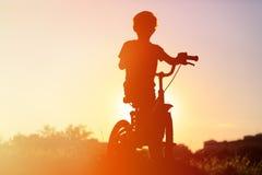 Weinig jongens berijdende fiets bij zonsondergang Stock Afbeeldingen