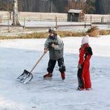 Weinig jongens schoonmakend ijs op vijver Royalty-vrije Stock Afbeelding