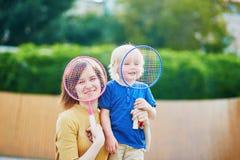Weinig jongens speelbadminton met mamma op de speelplaats Royalty-vrije Stock Foto