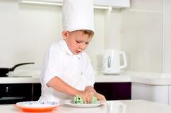Weinig jongenschef-kok die zijn platen schoonmaken terwijl het koken Royalty-vrije Stock Afbeeldingen