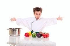 Weinig jongenschef-kok in het eenvormige koken Stock Fotografie