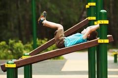 Weinig jongensoefening op de speelplaats Stock Foto's