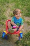 Weinig jongenspeuter die met kleurrijke children& x27 spelen; s plastic de bouwkruiwagen Stock Foto